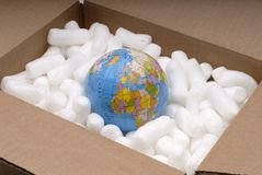 Shipping The World. The World Globe In A Shipping Carton With Packaging Peanuts stock photography