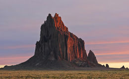 A Shiprock Landscape Against a Striated Sunrise Sky Royalty Free Stock Photo