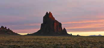 A Shiprock Landscape Against a Striated Sunrise Sky Stock Photography
