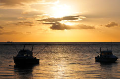 Ships. Two fishing boats near the coastline of Mauritius island in sunset stock photography