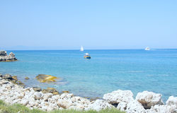 Ships in Aegean sea. Three various ships in blue Aegean sea with stone coastline in front Royalty Free Stock Images