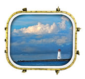 Ships Ahoy Lighthouse. Scenic lighthouse with dramatic cloudscape viewed from a ship port window Royalty Free Stock Image