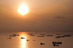 Ships anchored under setting sun Stock Image
