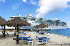 Ships and Beach. Two Cruise Ships docked next to a sandy beach with blue water and sky Royalty Free Stock Photos