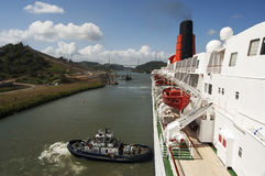 Ships bow in the Panama Canal crossing pushed by a tug. Royalty Free Stock Images