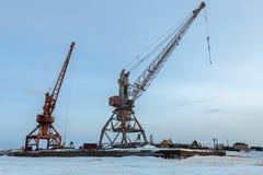 Ships cargo cranes on shore of Lake Baikal in winter. Stock Photos