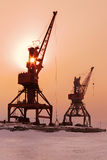 Ships cargo cranes on shore of Lake Baikal in winter at sunset. Royalty Free Stock Photography