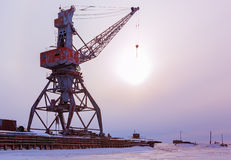 Ships cargo cranes on shore of Lake Baikal in winter at sunset. Stock Image
