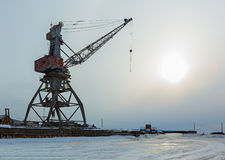 Ships cargo cranes on shore of Lake Baikal in winter at sunset. Royalty Free Stock Photos