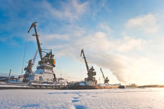 Ships cargo cranes on shore in winter at sunset. Ships cargo cranes on shore in winter Stock Images
