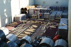 View of cargo holds with steel cargo. Stevedors are working into holds. royalty free stock photo