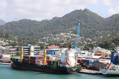 Cargo port in Castries, Saint Lucia. Ships and containers in a cargo port in Castries, the capital of Saint Lucia. In the background typical landscape of this Stock Photo