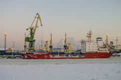 Ships and cranes in cargo port of St. Petersburg in winter time Royalty Free Stock Image