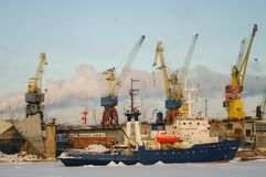 Ships and cranes in cargo port of St. Petersburg in winter time stock photo