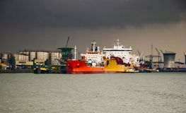 Ships at the dock. Ships in the sun with heavy rain in the background Royalty Free Stock Photos