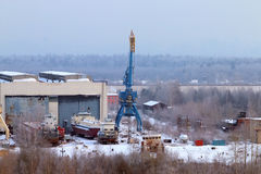Ships in dock with crane trucks and hangars Royalty Free Stock Images