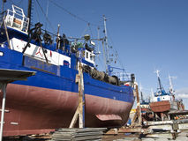 Ships in dry dock. Two large industrial fishing boats being repaired in a shipyard Royalty Free Stock Image