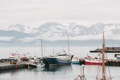 Ships in harbor and beautiful snow-covered mountains on horizon in husavik, iceland. HUSAVIK, ICELAND - 20 JULY, 2016: ships in harbor and beautiful snow-covered royalty free stock photo