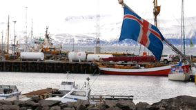 Ships harbor iceland flag. Ships in harbor of husavik in iceland flag stock footage