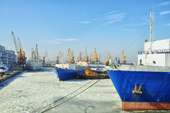 The ships have a cargo pier in winter. The sea covered by ice. Clear sunny cold winter day, blue sky. A lot of cargo cranes, ships at sea and at berth. Weekday stock photos