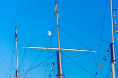 Ships mast. Daytime moon hiding behind a ships mast in a clear blue sky stock photos