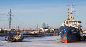 Ships moored in icy harbor Royalty Free Stock Photography