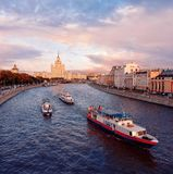 Ships on the Moscow River. View from the soaring bridge of the park `Zaryadye` to the skyscraper on Kotelnicheskaya embankment. stock image