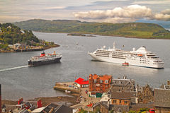 Ships at Oban. As the ferry leaves for the Western Isles, a cruise ship drops ancher at Oban on the Scottish west coast Stock Images