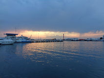 Ships at the pier in seaport at sunset. Ships at sea port Sochi, Russia, storm clouds at sunset Stock Image