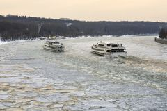 Ships sailing along the Moscow-River covered with ice floes towards each other. Moscow pleasure crafts sailing along the Moscow-River covered with broken ice Royalty Free Stock Photo