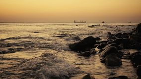 Ships in the sea and fishermen in a boat at sunset slow mo stock footage