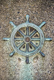 Ships steering wheel decoration on concrete wall Stock Photography