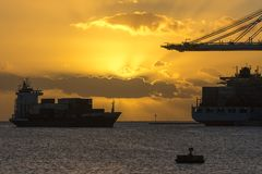 Ships at sunrise. Birzebbuga, Malta - December 17, 2017: A small container ship enters harbor to Malta Freeport just as the sun rises over the horizon Royalty Free Stock Images