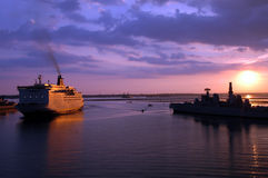 Ships at sunset. North Sea ferry and Royal navy ship at Portsmouth with sun setting behind royalty free stock image