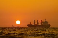 Ships and sunset. Oversea shipping ships running in the ocean, evening time Royalty Free Stock Images