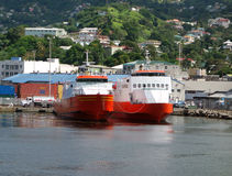 Ships tied stern to at a concrete wharf in the caribbean. Island ferries waiting to transport passengers and cargo throughout the grenadine islands stock photos