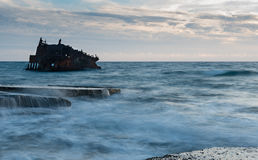 Shipwreck of an abandoned ship on a rocky shore Royalty Free Stock Images