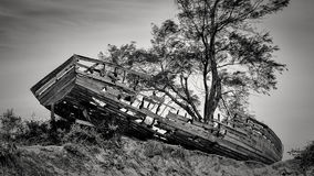 Shipwreck along the beach of Maputo Bay. An old wooden boat washed ashore and left abandoned on mound by the Maputo Bay beach Royalty Free Stock Photos