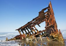 Shipwreck on a beach. Red and green rusty steel of a shipwreck on an ocean beach Stock Photography