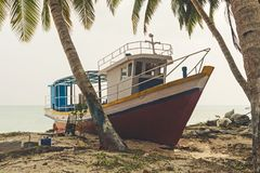 Shipwreck on a Beach. Large fishing boat on the sand on the beach under palm trees on the Indian island. The boat is under repair at the dock Stock Image