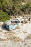 Shipwreck on beach, white sand, stones, plant around Stock Photos