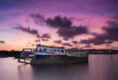 Shipwreck. The broken ship along with the sea and sunset twilight sky Stock Photos