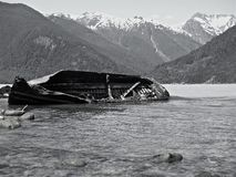 Shipwreck in icy sea. With snow capped mountains in background Stock Photos
