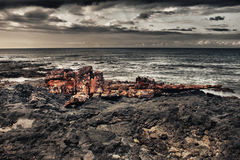 Shipwreck on a lava beach during storm. Shipwreck on a lava beach in Hawaii during storm Royalty Free Stock Images