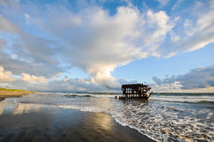 Shipwreck is pounded by waves on beach Royalty Free Stock Image