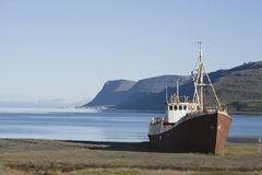 Shipwreck shore beach trawler in Westfjords Icelan. Rusting trawler beached on the remote shore of Patreksfjörður in the far north of the Westfjords of Iceland Royalty Free Stock Photo