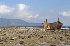 Shipwreck in shoreline. Old rusty shipwreck in low tide coastline Royalty Free Stock Photo
