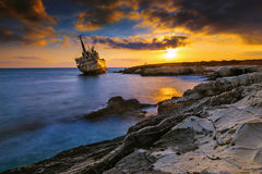 A Shipwreck by the shores of the Mediterranean sea in Cyprus at sunset Royalty Free Stock Image
