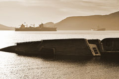 Shipwreck. View of an old rusty Shipwreck and other old cargo vessels in a calm bay Stock Photo