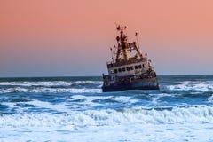 Shipwreck in wild Atlantic Ocean at Skeleton Coast, Namibia, Africa.  stock photography